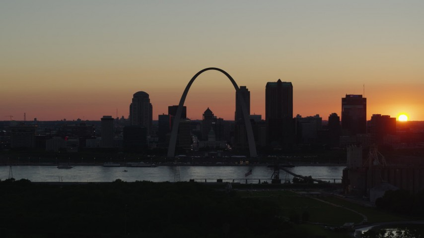 5.7K stock footage aerial video setting sun behind Downtown St. Louis, Missouri and the Gateway Arch Aerial Stock Footage | DX0001_000735