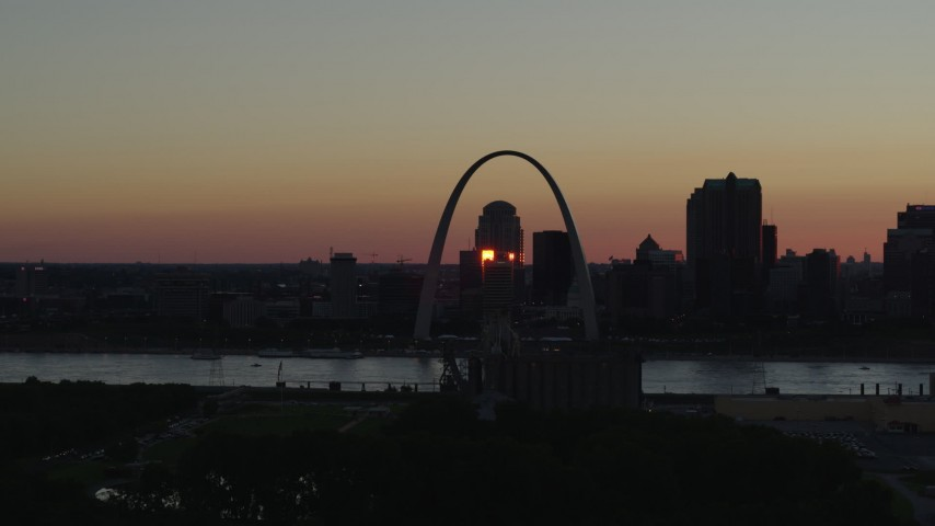 5.7K aerial video of passing the famous Arch across the river in Downtown St. Louis, Missouri, sunset Aerial Stock Footage | DX0001_000736