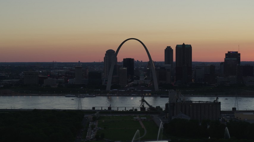 5.7K stock footage aerial video Gateway Arch seen from grain elevator across the river, and fountains, Downtown St. Louis, Missouri, twilight Aerial Stock Footage DX0001_000740