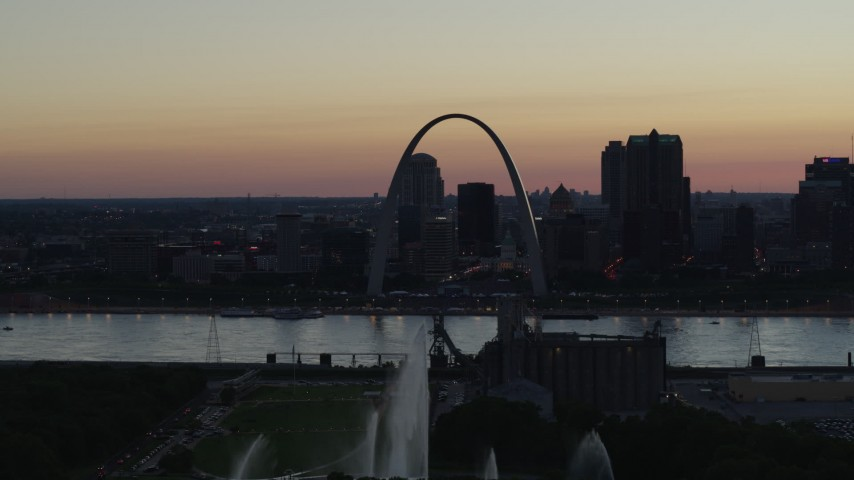 5.7K aerial video of a stationary view of the Gateway Geyser, and the Arch in Downtown St. Louis, Missouri, twilight Aerial Stock Footage | DX0001_000755