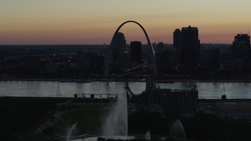 5.7K stock footage aerial video ascend over the Gateway Geyser for view of the Arch in Downtown St. Louis, Missouri, twilight Aerial Stock Footage DX0001_000758 | Axiom Images