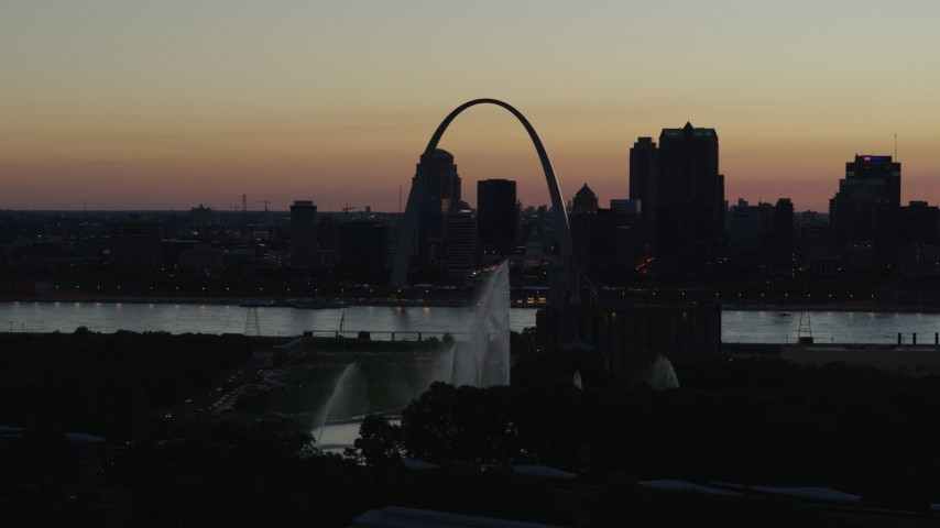 5.7K stock footage aerial video of the Gateway Arch beyond the Gateway Geyser in Downtown St. Louis, Missouri, twilight Aerial Stock Footage | DX0001_000760