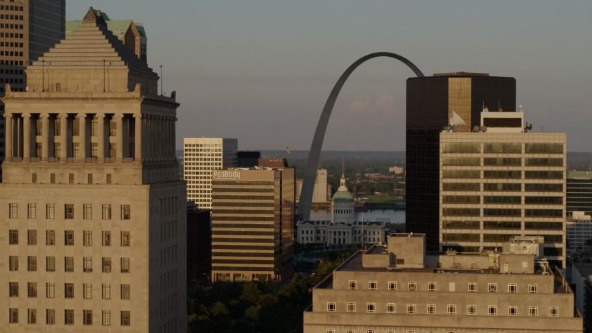 5.7K aerial video flyby office buildings, reveal Gateway Arch and museum at sunset, Downtown St. Louis, Missouri Aerial Stock Footage | DX0001_000840