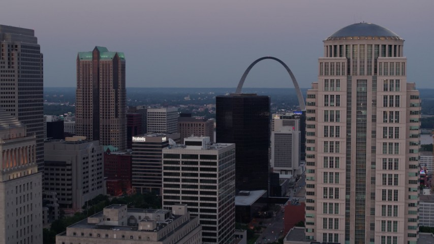 5.7K aerial video flyby courthouse skyscraper and reveal the Gateway Arch at twilight in Downtown St. Louis, Missouri Aerial Stock Footage | DX0001_000892