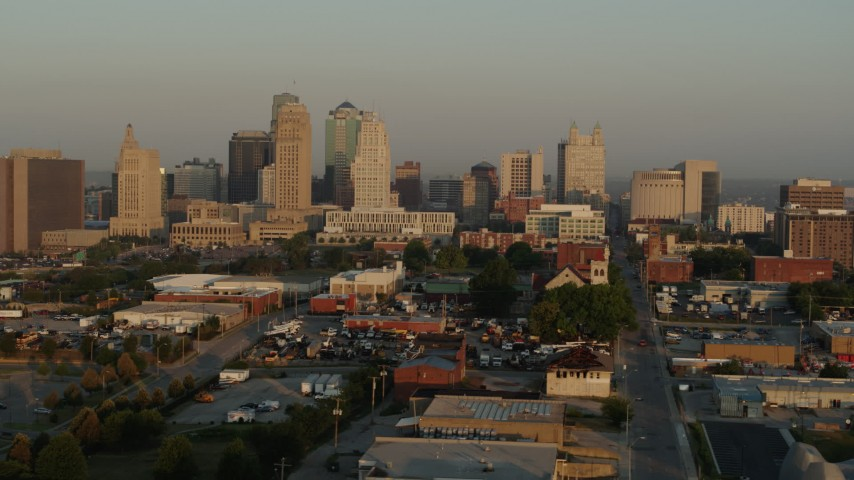 5.7K stock footage aerial video flying by the city skyline at sunrise, seen from an industrial area, Downtown Kansas City, Missouri Aerial Stock Footage | DX0001_001006