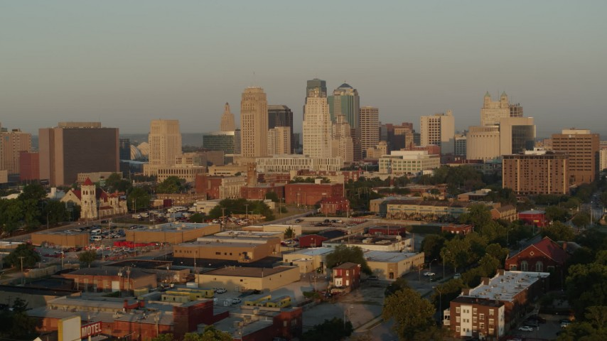 5.7K stock footage aerial video passing by the city skyline at sunrise, seen from an industrial area, Downtown Kansas City, Missouri Aerial Stock Footage | DX0001_001007