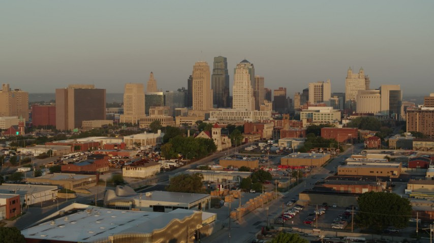 5.7K stock footage aerial video flyby and away from the city skyline at sunrise, seen from an industrial area, Downtown Kansas City, Missouri Aerial Stock Footage | DX0001_001008