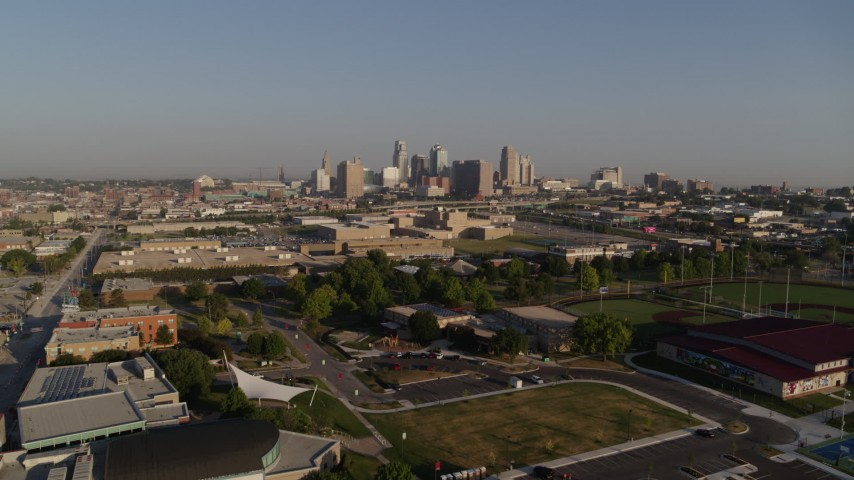 5.7K stock footage aerial video of flying over a community center to approach skyline of Downtown Kansas City, Missouri Aerial Stock Footage | DX0001_001033