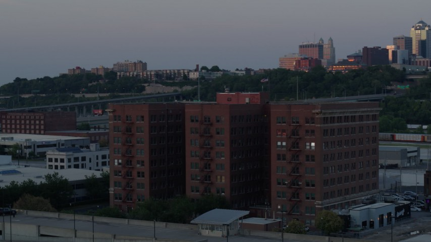 5.7K stock footage aerial video orbit front of brick office building at twilight, city skyline in background, Kansas City, Missouri Aerial Stock Footage | DX0001_001186