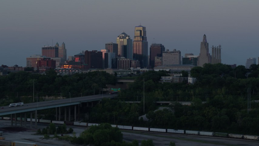 5.7K stock footage aerial video of the city skyline at twilight while flying near freeway in Downtown Kansas City, Missouri Aerial Stock Footage | DX0001_001193