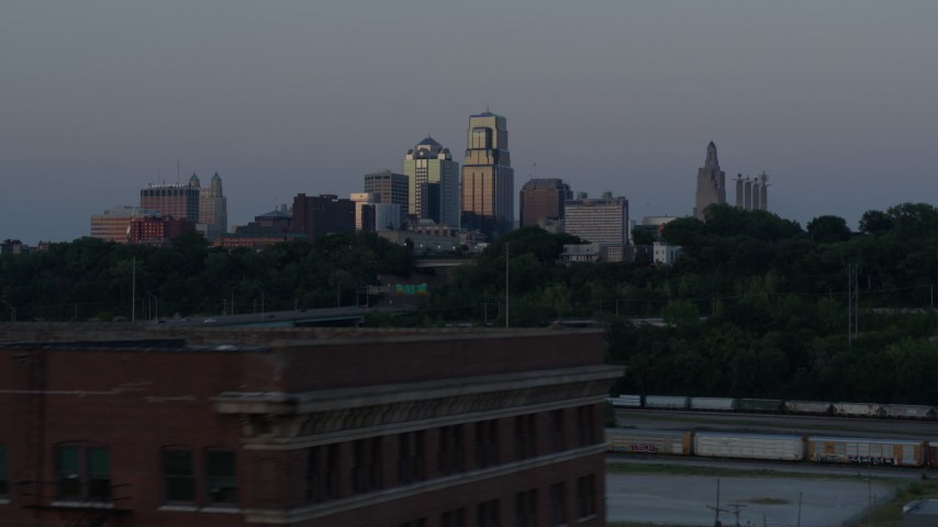 5.7K stock footage aerial video of the city skyline at twilight while descending to reveal brick building, Downtown Kansas City, Missouri Aerial Stock Footage | DX0001_001194