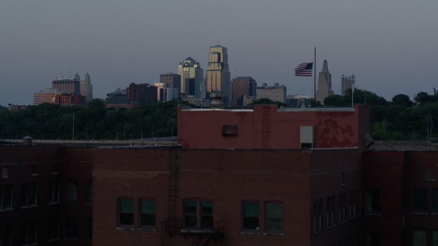 5.7K stock footage aerial video ascend by brick building at twilight, reveal skyline of Downtown Kansas City, Missouri Aerial Stock Footage | DX0001_001198
