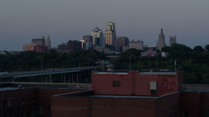 5.7K stock footage aerial video of the skyline at twilight, descend to reveal brick building, Downtown Kansas City, Missouri Aerial Stock Footage | DX0001_001199