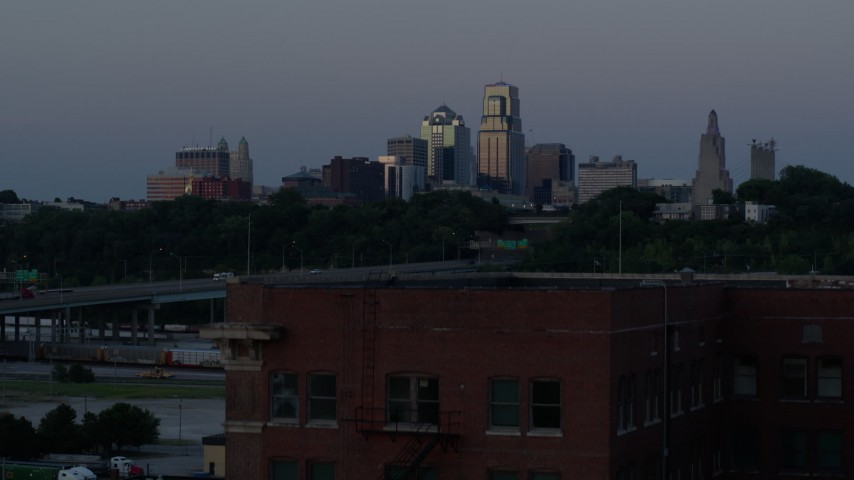 5.7K stock footage aerial video descend with view of skyline at twilight, reveal brick building, Downtown Kansas City, Missouri Aerial Stock Footage | DX0001_001203
