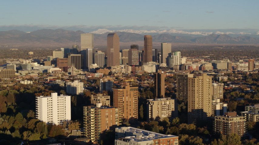 5.7K stock footage aerial video of skyscrapers in Downtown Denver, Colorado at sunrise, seen while passing apartment buildings Aerial Stock Footage | DX0001_001413