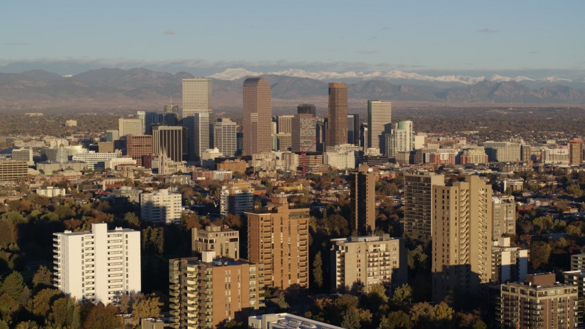 5.7K stock footage aerial video of tall skyscrapers in Downtown Denver, Colorado at sunrise, seen while flying past apartment buildings Aerial Stock Footage | DX0001_001416