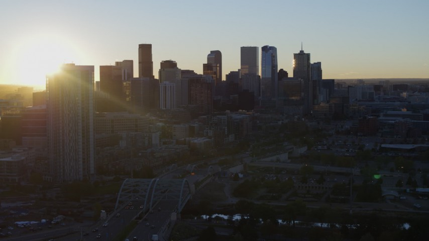 5.7K stock footage aerial video descend with view of the sun behind the city skyline at sunrise in Downtown Denver, Colorado Aerial Stock Footage | DX0001_001616