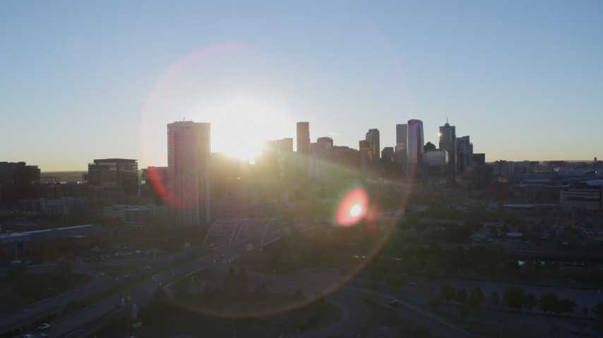 5.7K stock footage aerial video ascend for stationary view of bright sun and city skyline at sunrise in Downtown Denver, Colorado Aerial Stock Footage | DX0001_001621