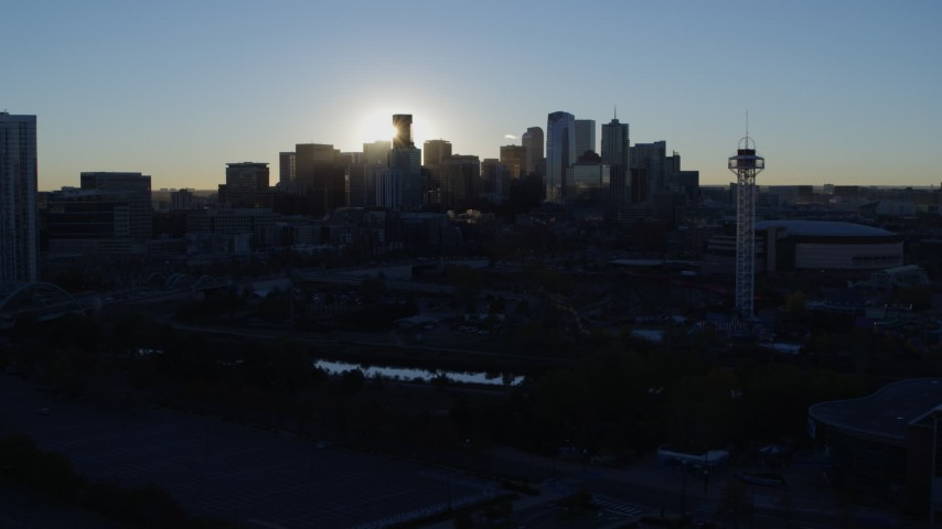5.7K stock footage aerial video of sun and city skyline, seen while flying by theme park and arena at sunrise in Downtown Denver, Colorado Aerial Stock Footage | DX0001_001624