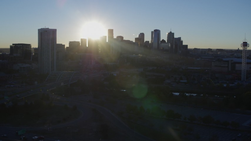 5.7K stock footage aerial video of sun and city skyline, seen while descending near a skyscraper at sunrise in Downtown Denver, Colorado Aerial Stock Footage | DX0001_001626