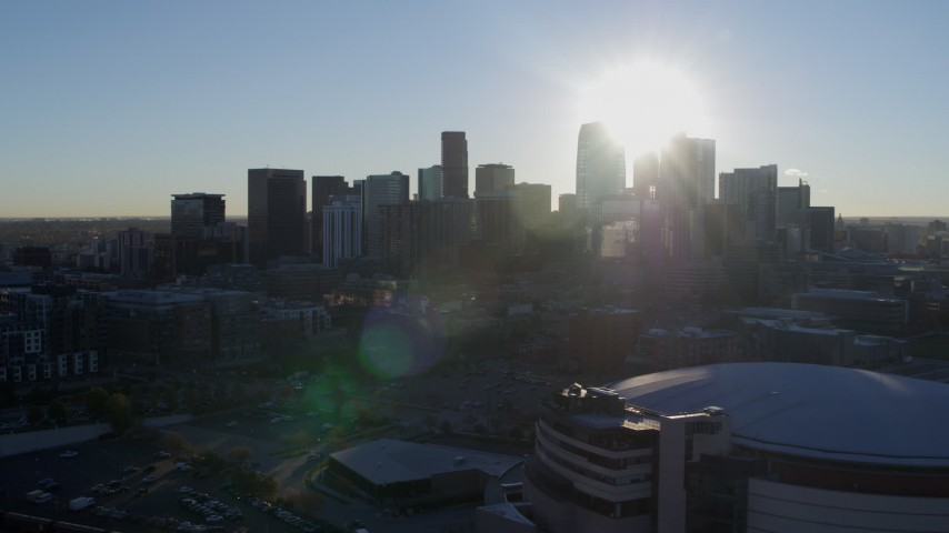 5.7K stock footage aerial video of the rising sun behind the city skyline, seen from arena in Downtown Denver, Colorado Aerial Stock Footage | DX0001_001628