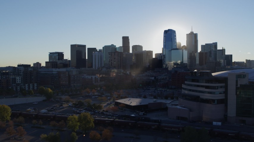 5.7K stock footage aerial video flyby the rising sun behind the city skyline, reveal the arena in Downtown Denver, Colorado Aerial Stock Footage | DX0001_001631