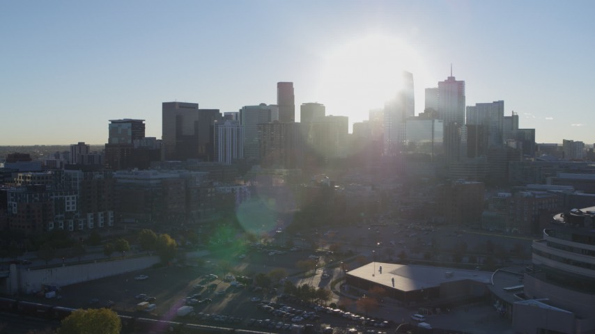 5.7K stock footage aerial video flyby arena to focus on sun behind city's skyline at sunrise in Downtown Denver, Colorado Aerial Stock Footage | DX0001_001632