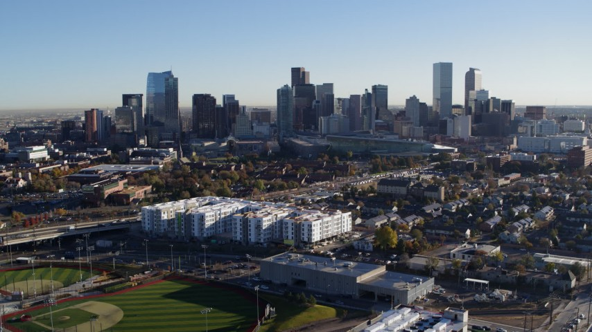 5.7K stock footage aerial video ascend to reveal and focus on the city skyline at sunrise in Downtown Denver, Colorado Aerial Stock Footage DX0001_001642