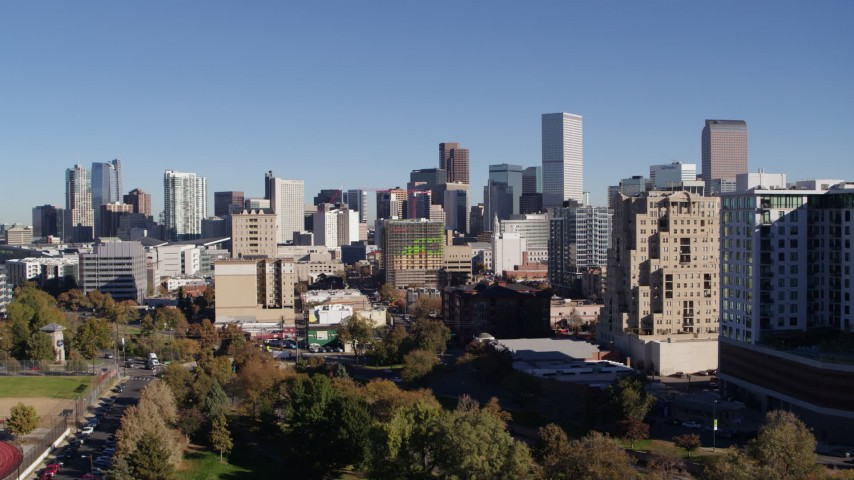 5.7K stock footage aerial video reverse view of the city's skyline while descending near office buildings, Downtown Denver, Colorado Aerial Stock Footage | DX0001_001673