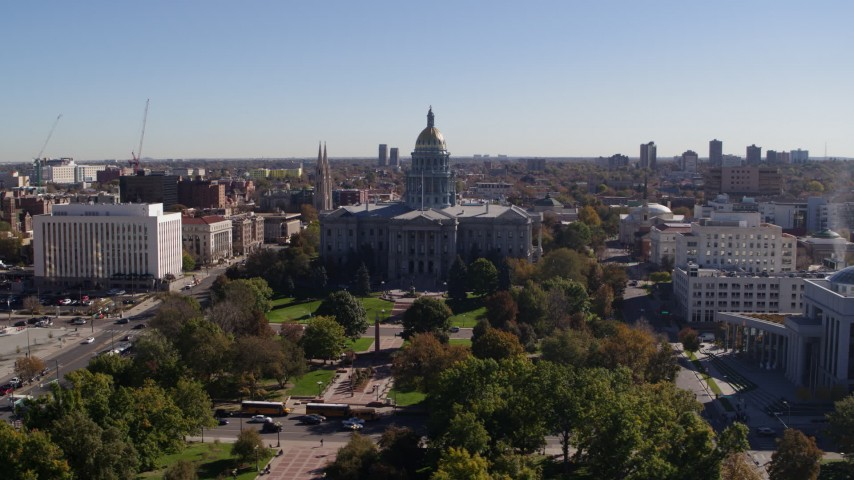 5.7K stock footage aerial video of the Colorado State Capitol building, seen while flying over park, Downtown Denver, Colorado Aerial Stock Footage | DX0001_001690