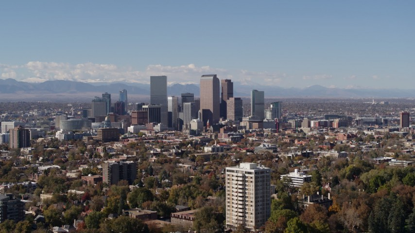 5.7K stock footage aerial video flying by the city's skyline, with the mountains in background, Downtown Denver, Colorado Aerial Stock Footage DX0001_001734 | Axiom Images