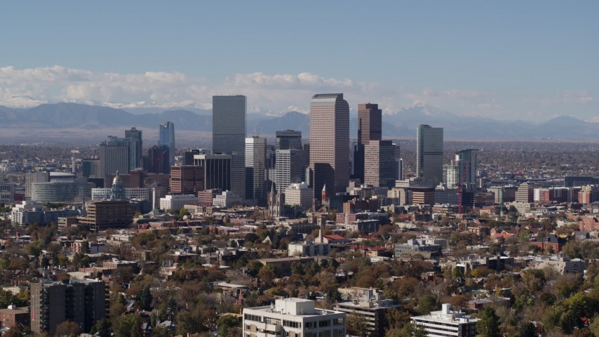 5.7K stock footage aerial video slow descent by the city's skyline with mountains in background, Downtown Denver, Colorado Aerial Stock Footage DX0001_001740 | Axiom Images