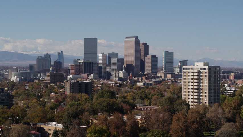 5.7K stock footage aerial video descend while focusing on the city's skyline with mountains in distance, Downtown Denver, Colorado Aerial Stock Footage | DX0001_001743