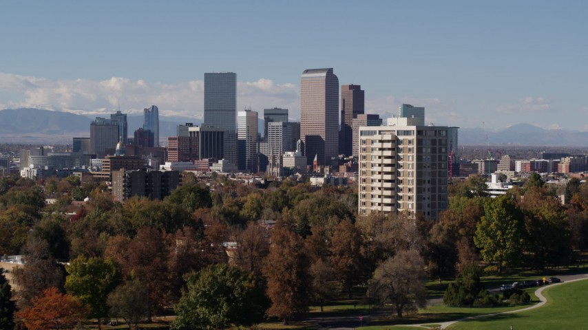 5.7K stock footage aerial video ascend while focusing on the city's skyline with mountains in distance, Downtown Denver, Colorado Aerial Stock Footage | DX0001_001744