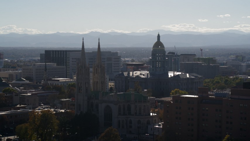 5.7K stock footage aerial video of the Colorado State Capitol seen while passing cathedral, Downtown Denver, Colorado Aerial Stock Footage | DX0001_001757