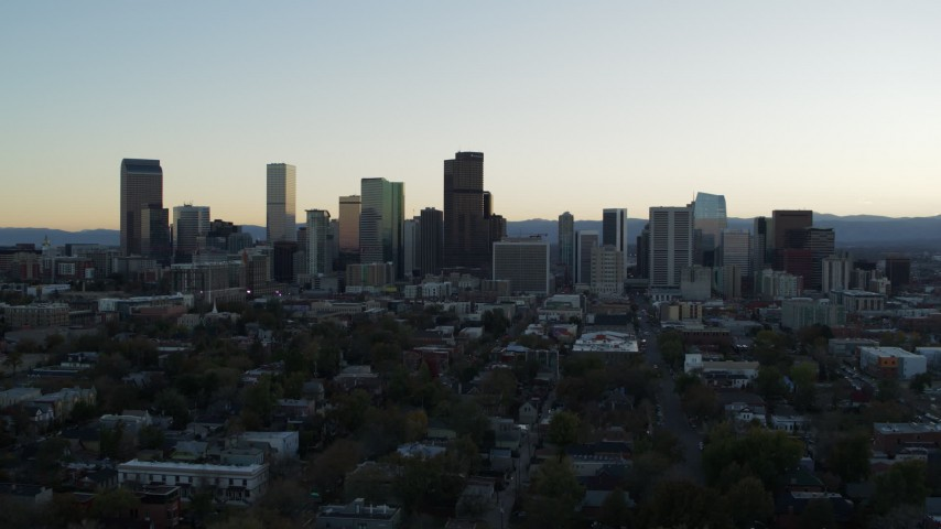 5.7K stock footage aerial video of the city skyline at sunset while descending and flying away, Downtown Denver, Colorado Aerial Stock Footage | DX0001_001833