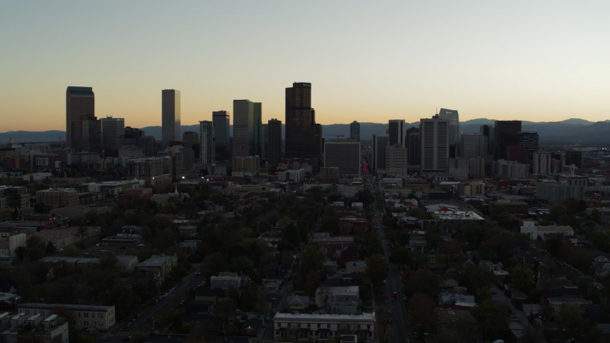 5.7K stock footage aerial video fly away from the city skyline at sunset, descend toward trees in Downtown Denver, Colorado Aerial Stock Footage | DX0001_001844
