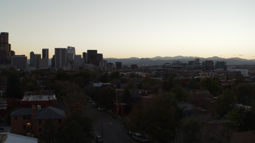 5.7K stock footage aerial video of pan across apartment buildings to reveal the city's skyline at sunset, Downtown Denver, Colorado Aerial Stock Footage | DX0001_001848