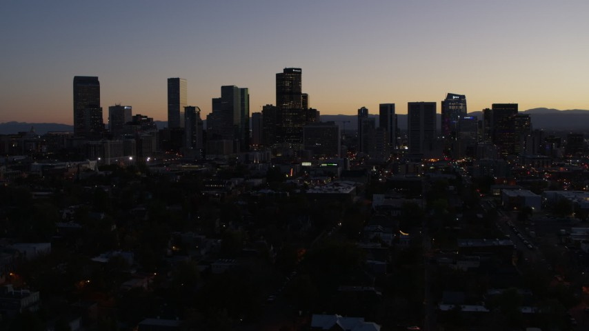 5.7K stock footage aerial video flying by the city's skyline at twilight and descend, Downtown Denver, Colorado Aerial Stock Footage | DX0001_001868