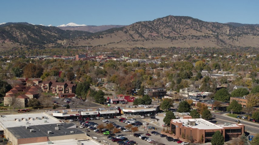 5.7K stock footage aerial video of flying by the mountain town of Boulder, Colorado before descending Aerial Stock Footage | DX0001_001956