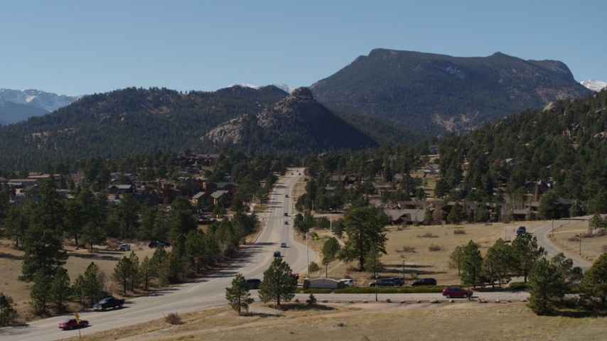 5.7K aerial video reverse view of cars on a road through the town of Estes Park, Colorado Aerial Stock Footage | DX0001_001977