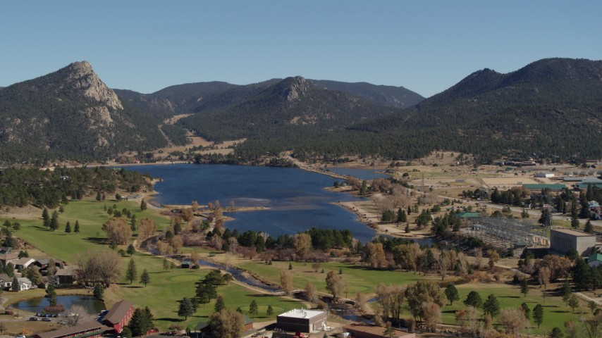 5.7K aerial video fly away from Lake Estes, by golf course and green mountains in Estes Park, Colorado Aerial Stock Footage | DX0001_001981