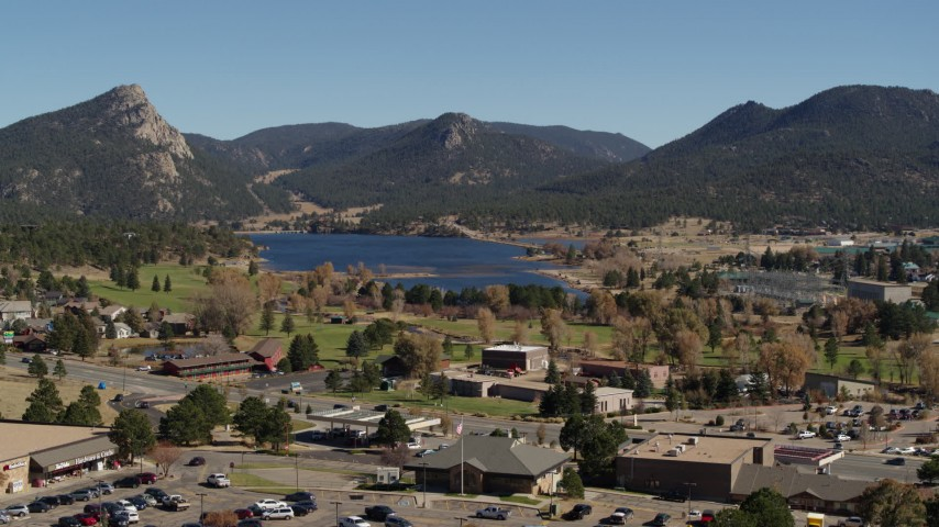 5.7K aerial video of Lake Estes, by golf course and green mountains while descending in Estes Park, Colorado Aerial Stock Footage | DX0001_001982