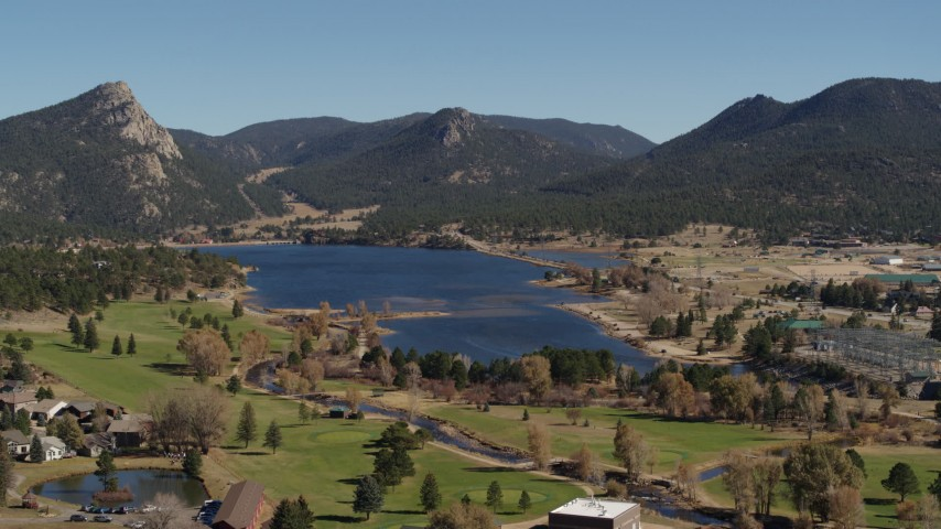 5.7K aerial video descend with focus on Lake Estes, golf course and green mountains in Estes Park, Colorado Aerial Stock Footage | DX0001_001984