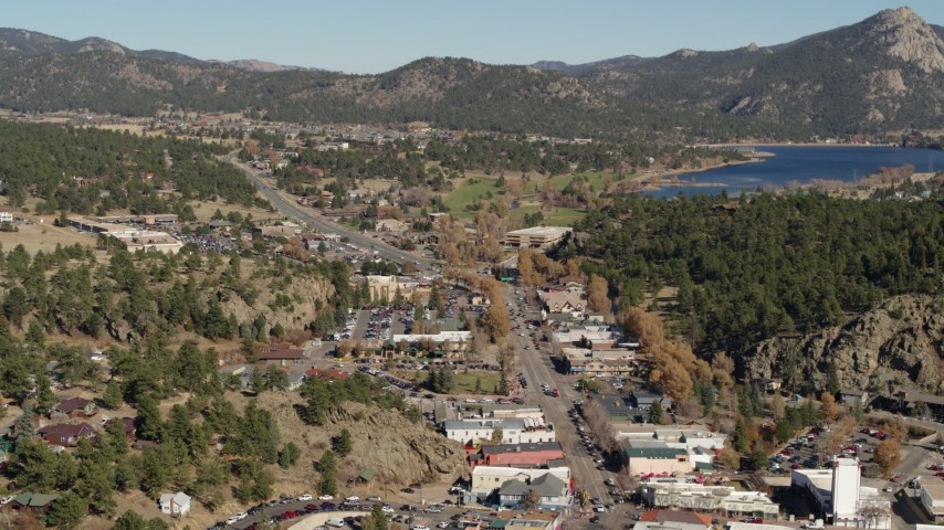 5.7K aerial video flyby shops lining road through Estes Park, Colorado lake and mountains in distance Aerial Stock Footage | DX0001_001998