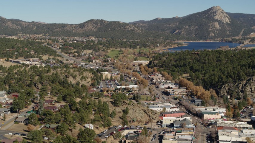 5.7K aerial video a view of shops lining road through Estes Park, Colorado lake and mountains in distance Aerial Stock Footage | DX0001_001999