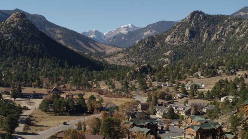 5.7K aerial video of rural homes near rugged mountains in Estes Park, Colorado seen while ascending Aerial Stock Footage | DX0001_002002