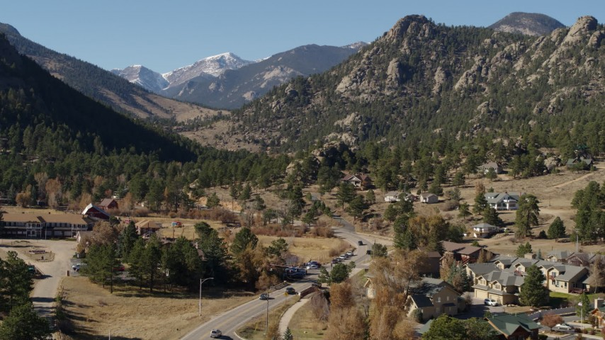 5.7K aerial video flyby rural homes near rugged mountains in Estes Park, Colorado seen while descending Aerial Stock Footage | DX0001_002003