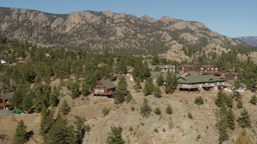 5.7K stock footage aerial video orbiting rural hillside homes near rugged mountains in Estes Park, Colorado Aerial Stock Footage | DX0001_002004
