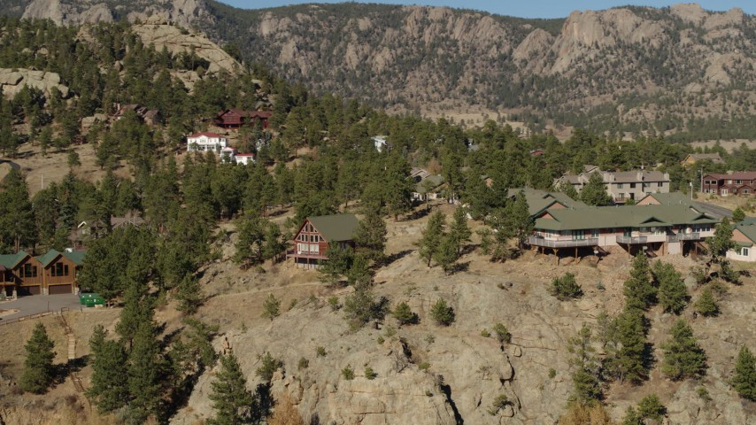 5.7K aerial video orbit rural hillside homes near rugged mountains in Estes Park, Colorado Aerial Stock Footage | DX0001_002005